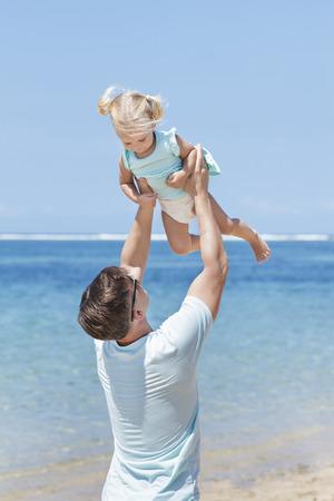 niñas pequeñas: cerca retrato de joven padre se divierte con su pequeña hija en la playa