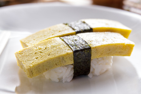 nigiri: close up portrait of japanese food tamago nigiri sushi on white plate