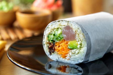 hashi: close up portrait of sushi burrito roll on shiny black plate