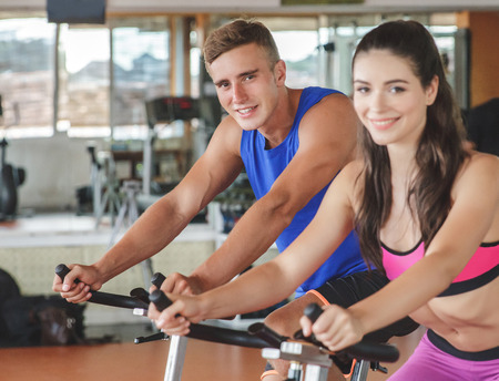 life partner: portrait of sporty woman using cycling exercise bike with her fitness partner