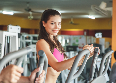 young women: portrait of beautiful sporty woman exercising on fitness machine Stock Photo