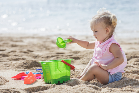 portrait of little girl playing sand toys at the beach