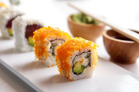 california roll: portrait of japanese cuisine california roll and tuna avocado roll on white plate served with wasabi and soy sauce