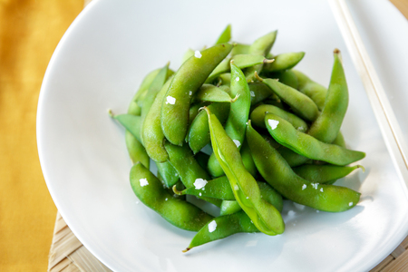 nibbles: close up portrait of japanese food edamame nibbles, boiled green soy beans Stock Photo