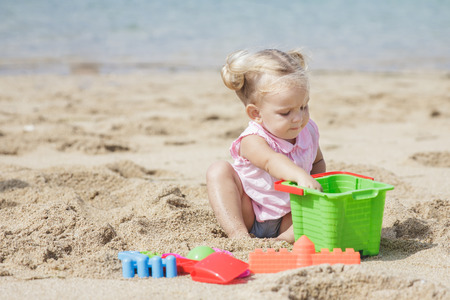 portait: portait of little girl playing sand toys at the beach with copy space