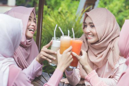portret van mooie Aziatische moslimvrouw met plezier in café samen met vrienden