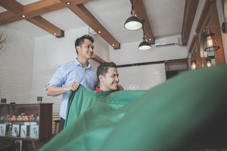 hair cover: Young handsome barber put a sheet to cover his client from cutted hair