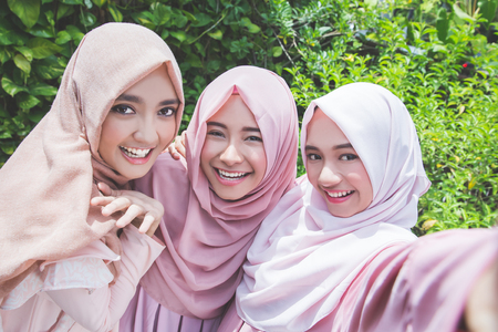 camera girl: asian girl friends with head scarf taking selfie together Stock Photo