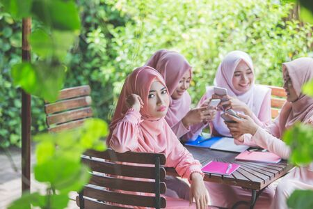 group of young girl using their own smartphone and ignoring her friend Stock Photo