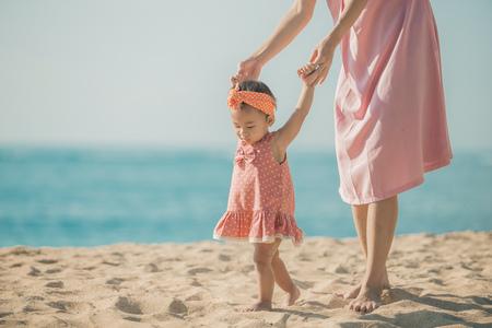 Retrato de una madre está enseñando a su hija camina en la playa Foto de archivo - 66164044