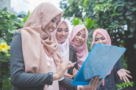 group of four young muslim businesswoman having a meeting outdoor
