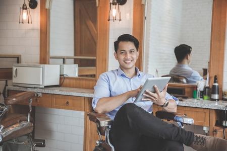 理髪店で座りながらタブレット pc を持って幸せな若い男。デジタル テクノロジーとマーケティング ビジネス