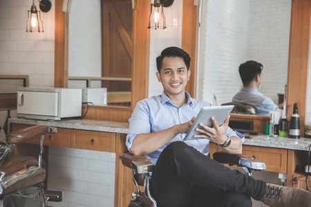 happy young man holding tablet pc while sitting at barbershop. business marketing with digital technology Stock Photo