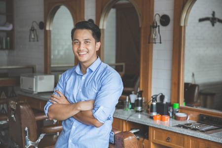 自信を持って床屋専門家です。若い男はカメラを見て、笑みを浮かべて立っている理髪店で 写真素材