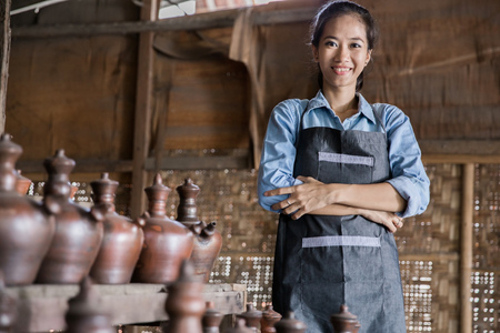 portrait of Smiling female potter proudly standing in her pottery workshop