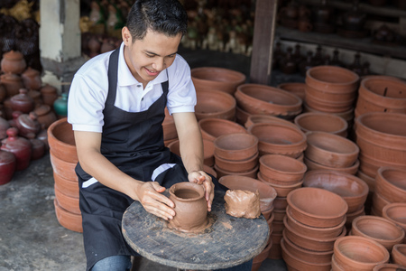 sculptor: craftsman artist making pottery vase from fresh wet clay on pottery wheel Stock Photo
