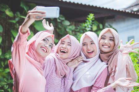 asian girl friends with head scarf taking selfie together 版權商用圖片