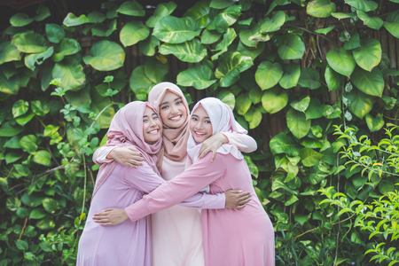 group of attractive asian woman with hijab together. best friend hugs each other Banco de Imagens