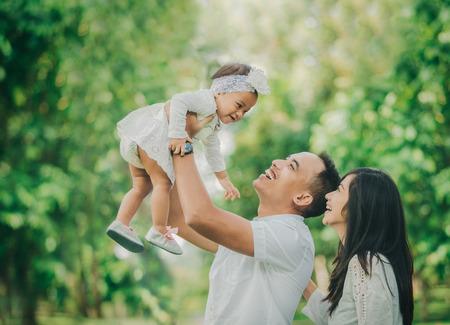 一緒に楽しい公園にかわいい赤ちゃんと美しい家族の肖像 写真素材
