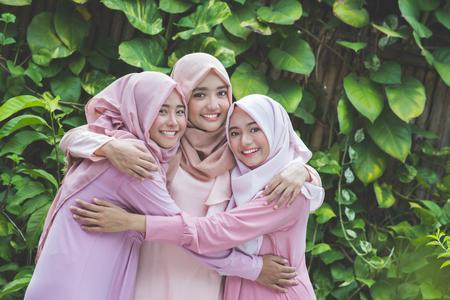 Retrato de grupo feliz de chica guapa mejores amigos juntos. concepto de mujer musulmana vistiendo hiyab o pañuelo de cabeza Foto de archivo - 66164121