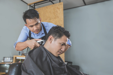 portrait of Young handsome barber making haircut of attractive man in barbershop