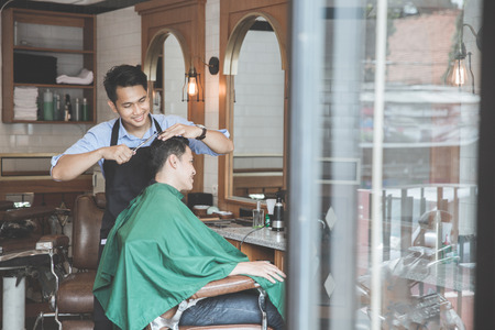Cheerful young man getting haircut by hairdresser at barbershop