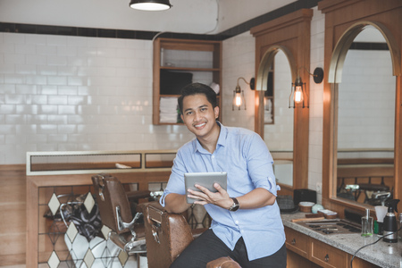 Confident barber expert. Young man with tablet pc smiling while standing at barbershop