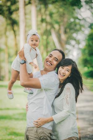 Ritratto di bella famiglia con bambino sveglio nel parco divertirsi insieme Archivio Fotografico - 66164155