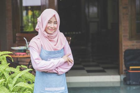 portret van trotse jonge ondernemer die zich voor haar winkel