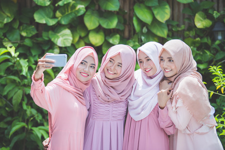 head scarf: asian girl friends with head scarf taking selfie together Stock Photo