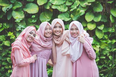 Retrato de grupo feliz de chica guapa mejores amigos juntos. concepto de mujer musulmana vistiendo hiyab o pañuelo de cabeza Foto de archivo - 66164161