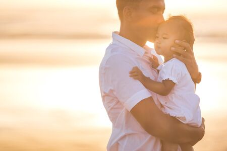 family with baby: portrait of a Father and little baby daughter on beach at sunset Stock Photo