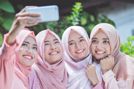 excited young muslim girl friends taking selfie together outdoor