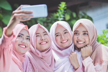 opgewonden jonge moslim meisje vrienden nemen selfie samen buiten