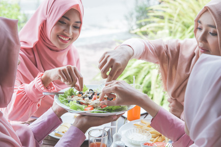 healthy young muslim woman having fruit and vegetable salad for lunch