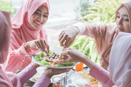 Mujer joven musulmana sana que tiene la ensalada de la fruta y verdura para el almuerzo Foto de archivo - 66164179
