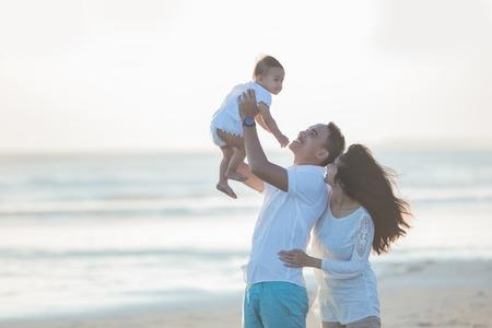 幸せな家族と夏のレジャーでの夕日を楽しむ赤ちゃんの肖像画 写真素材
