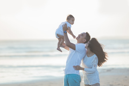portrait of happy family and baby enjoying sunset in the summer leisure Banco de Imagens