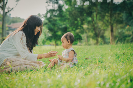 portrait of Beauty Mother and her Child playing in Park together Foto de archivo