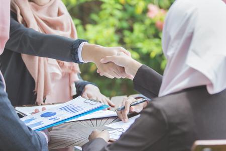 自信を持って若いイスラム教徒のビジネス女性が握手します。チームワークの契約概念 写真素材