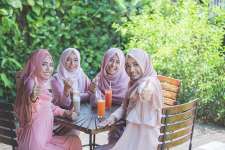 female hands: group of asian woman with hijab showing thumbs up to camera while sitting in cafe