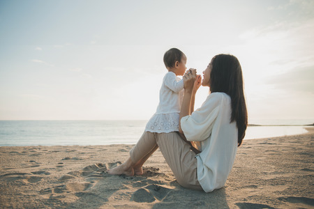 美しい母と赤ちゃんの屋外。母と彼女の子供を一緒に夕日を楽しむ
