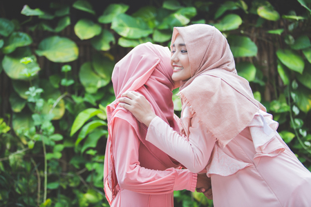portrait of a girl embracing her friend. muslim woman with hijab