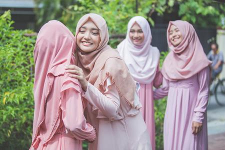 portret van een meisje omarmen haar vriend. moslim vrouw met hijab