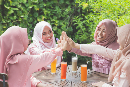 head scarf: asian woman best friends putting hands together at cafe. female with head scarf