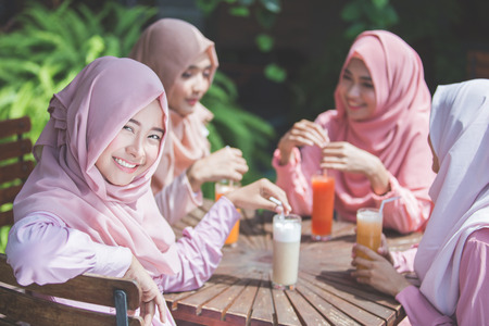 portrait of pretty asian muslim woman having fun in cafe together with friends Stock Photo