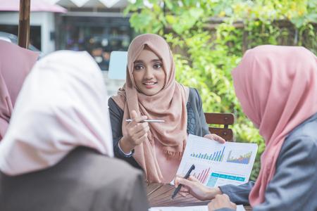 Groep van vier jonge zakenvrouw met een bijeenkomst in een coffeeshop Stockfoto - 66164262