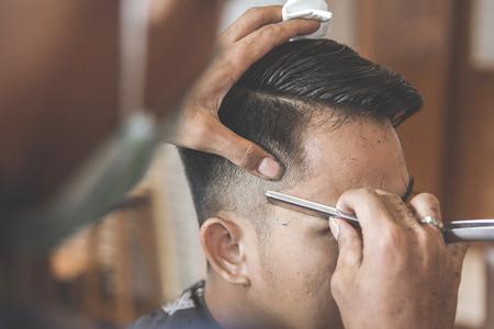 man getting his hair cut at barbershop Foto de archivo
