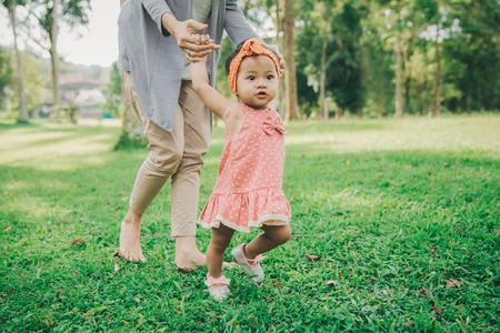 Haciendo lindo bebé feliz divertida sus primeros pasos en una hierba verde, madre sosteniendo sus manos por el apoyo a aprender a caminar Foto de archivo - 66164273