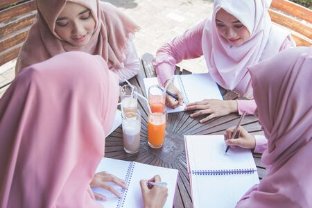 head scarf: young asian student with head scarf studying together in a cafe